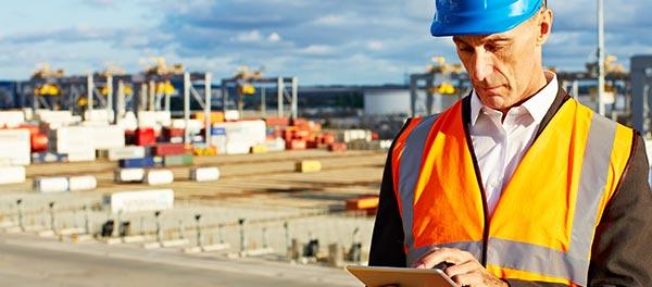 Inspector at a commercial dock, wearing a hi-vis vest and hard hat, checks details on a tablet