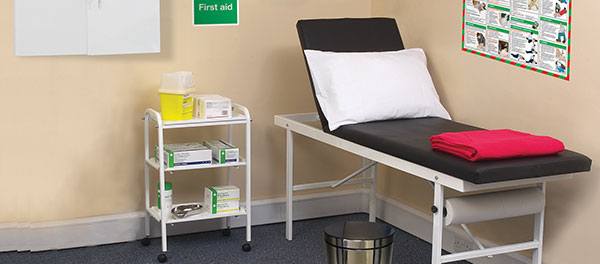 First aid room consisting of couch, bin, signs, storage wall cabinet and instrument trolley