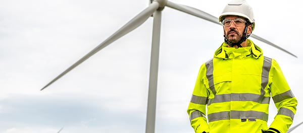 Man wearing hi-vis jacket and trousers and PPE stood in a farmer's field in front of a wind turbine