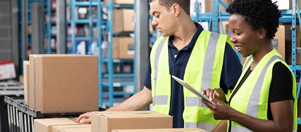 Two warehouse distribution workers wearing hi-vis vests, checking packed boxes on a conveyor