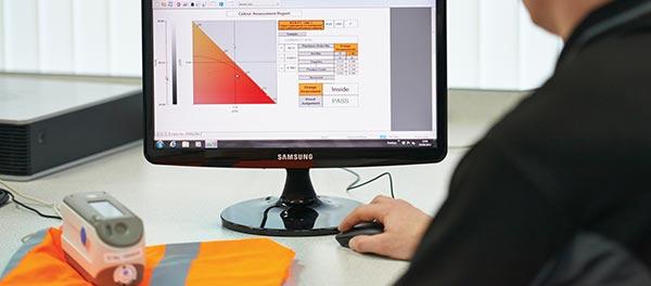 Testing the colour of a hi-vis vest in Arco's laboratory, to ensure it meets EN 20471 standard