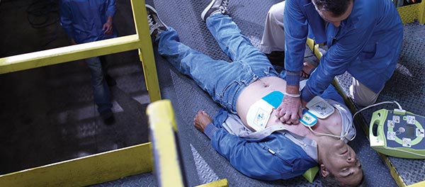 Worker applying Defibrillator and resuscitation to collapsed worker