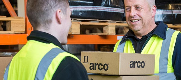 Box of new Arco hi-vis garments being handed to a warehouse worker