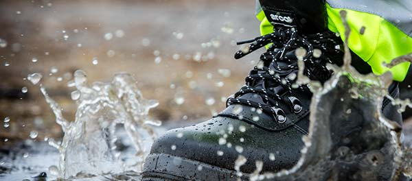 Worker in hi-viz trousers and black safety boots stepping in a muddy puddle